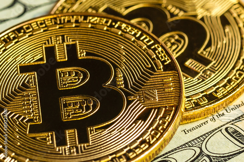 фотография  Gold bitcoin on a white background next to us paper money with a face value of d