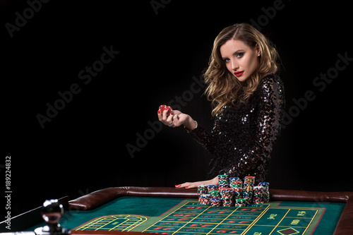 Fotomural Woman playing in casino. Woman stakes piles of chips playing rou