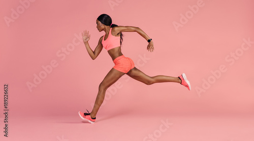 Young athlete running indoors Wallpaper Mural
