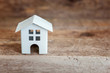 Miniature white toy house on a wooden table. Mortgage property insurance dream home concept