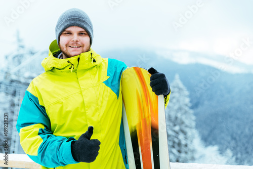 fototapeta na ścianę man stands with snowboard on the top of the hill
