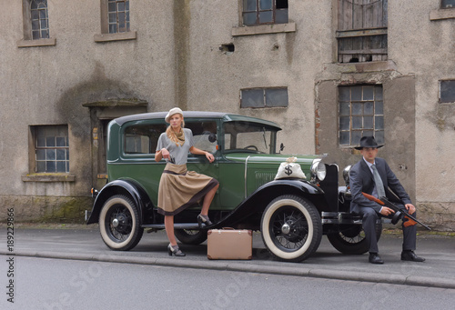 Fotografia  Two models get dressed up in 1930's style vintage fashion clothes and act the role of the gangster duo Bonnie and Clyde