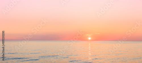 Spoed Foto op Canvas Zee zonsondergang Sun Is Setting On Horizon At Sunset Sunrise Over Sea Or Ocean.