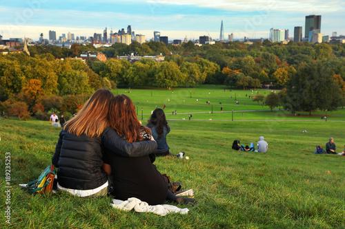 People resting on Primrose Hill at sunset, London, UK