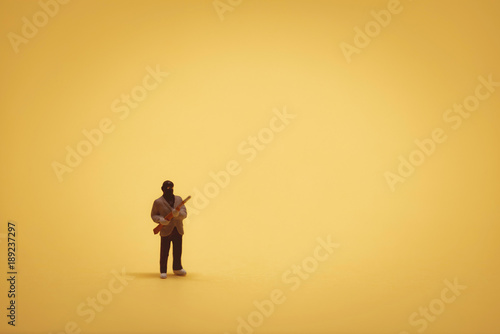 Fotomural  Miniature burglar with shotgun on yellow backgound
