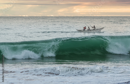 Fotografie, Obraz  Three men sailing for fishing in ocean at the sunset