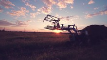 Farm Tractor Transports A Stack Of Straw Through The Field At Sunset