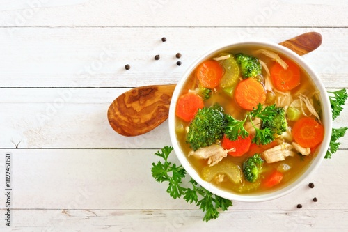 Homemade chicken vegetable soup, overhead view on a white wood background