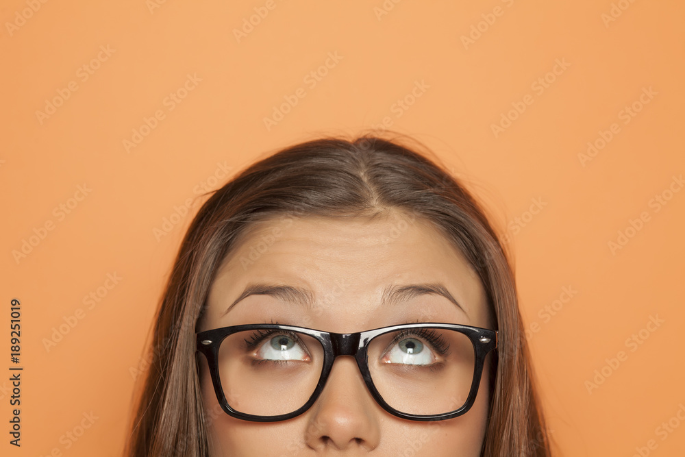 Fototapeta half portrait of a young girl with glasses looking up