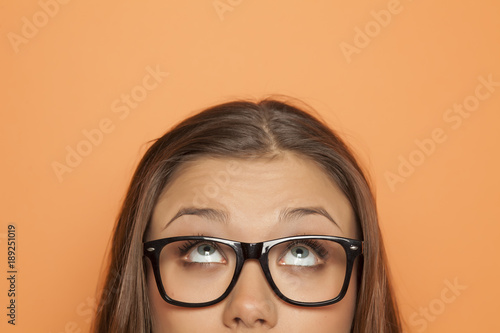Fotografie, Obraz  half portrait of a young girl with glasses looking up