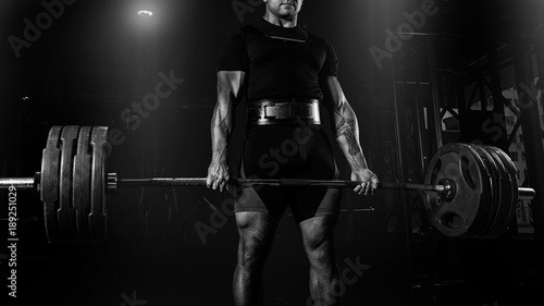 Fotografia  Professional athlete is standing and is holding a very heavy barbell