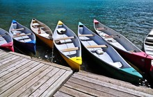 Abstract Of Colorful Boats Docked Ready For Tourist Canoeing Experience At Most Beautiful Moraine Lake In Banff National Park, Alberta, Canada