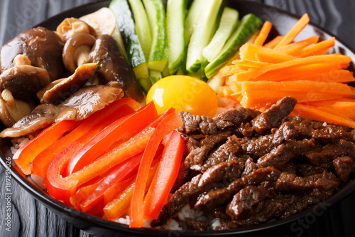 Delicious Bibimbap with beef, egg, vegetables, shiitake and rice close-up in a bowl on the table. horizontal