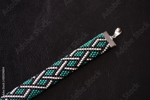 Green bead crochet bracelet with celtic print on a dark background close up Wallpaper Mural