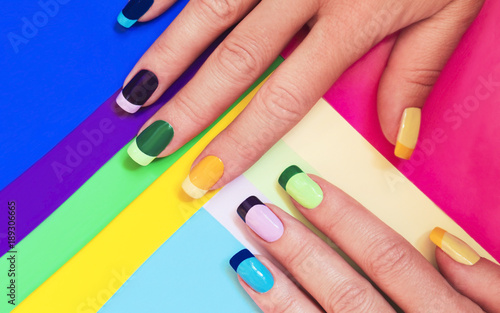 Staande foto Manicure Multi-colored pastel manicure combined tone on tone with a striped background.Nail art.