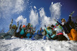 canvas print picture - A group of friends of skiers and snowboarders fun throwing snow on top of the mountain.
