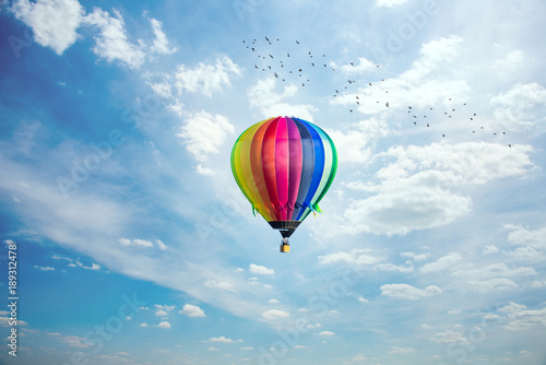 Colorful hot-air balloon riding across blue sky