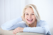 canvas print picture - Active beautiful middle-aged woman smiling friendly and looking in camera. Woman's face closeup. Realistic images without retouching with their own imperfections. Selective focus.