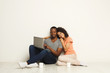 Happy african-american couple shopping online on laptop