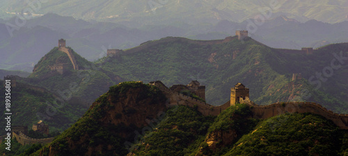 Obraz na płótnie The Great Wall of China weaving through the mountains with a hazy background at