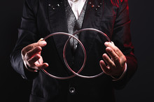Magician Shows Trick With Metal Rings. Manipulation With Props. Sleight Of Hand.