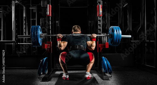 Keuken foto achterwand Fitness Professional athlete sits with a barbell on his shoulders and prepares to stand with her.