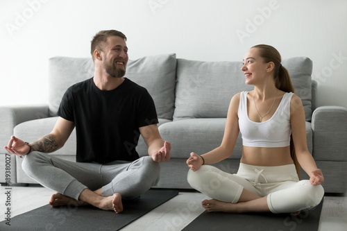 Young happy couple having fun doing yoga together at home sitting on mat in lotus pose looking at each other smiling, positive man and woman learning to meditate, healthy mindful lifestyle habits
