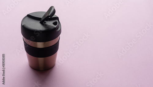 Close up of reusable coffee cup on pink background from above