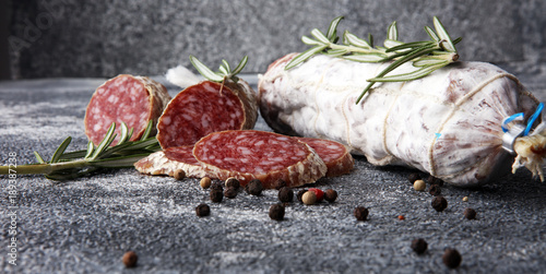 sliced salami and salami sausage on grey background