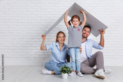 Obraz concept housing   young family. Mother father and child in new house with  roof at empty brick wall - fototapety do salonu