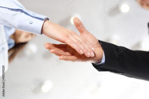 Fototapeta Gratulacje. Powitanie nowego pracownika firmy. Dłoń kobiety i mężczyzny w  strojach biurowych podczas gestu przywitania. obraz