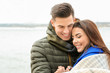 Beautiful couple in warm clothes near river