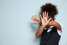 """Little African-American Girl With Phrase """"Stop Bullying"""" On Light Background"""