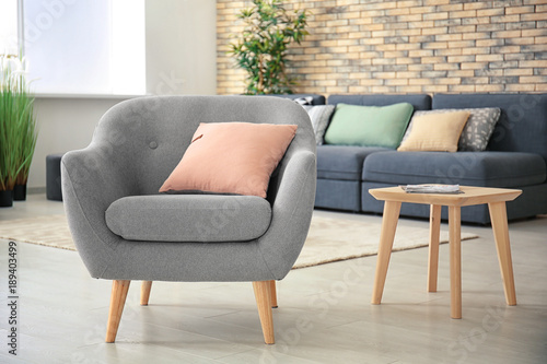 Photo Comfortable armchair with pillow in room