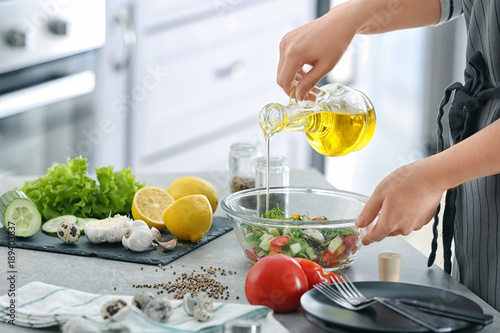 Woman pouring oil into bowl with fresh vegetable salad on table