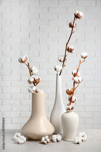 Photo  Cotton flowers in vases on table