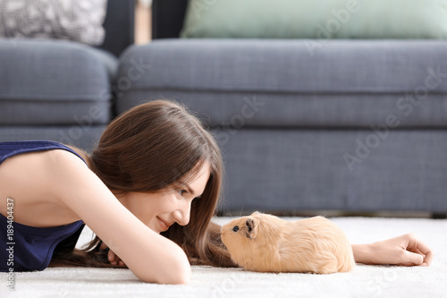 Beautiful young woman with pet guinea pig at home