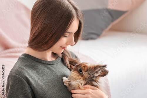 Beautiful young woman with pet rabbit at home