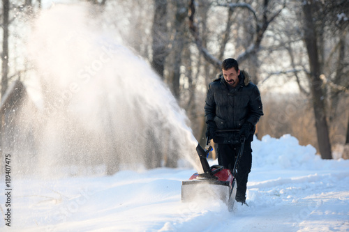 Snow removal with a snow blower Canvas Print