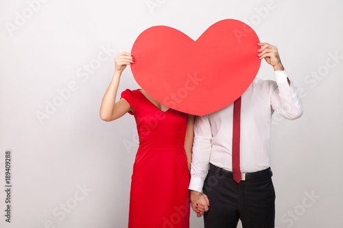 Photo  Unknown couple hide and seek behind big red heart