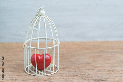 Fotografia  Red heart inside the miniature birdcage, love/ romance or anchoring in the pasat