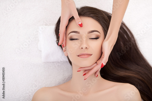 Woman under professional facial massage in beauty spa