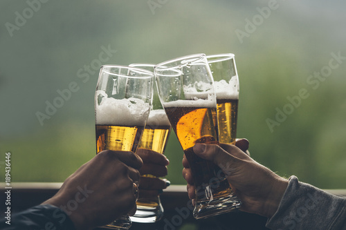 Photo sur Aluminium Biere, Cidre Beer with foam light tall boys in the hands of friends raising a toast closeup