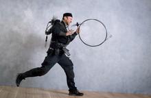 Springender Schornsteinfeger In Arbeitskleidung Und Mit Kehrgeräten Vor Betonwand