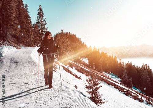 Woman hiking along trail in snowy mountains