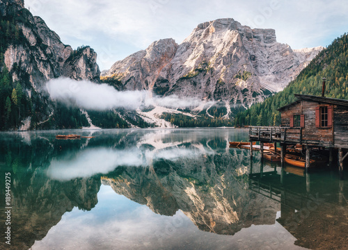 Poster Bergen Panoramic view of Braies Lake with the hut and boats in Dolomites mountains and Seekofel in the morning, Pragser Wildsee, South Tirol, Italy
