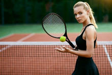 Woman Playing Tennis On Court.