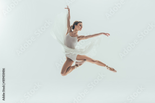 Fotografie, Tablou  young elegant ballerina in white dress jumping in studio, isolated on white