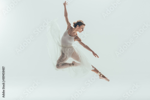 Photo beautiful ballet dancer in white dress jumping in studio, isolated on white