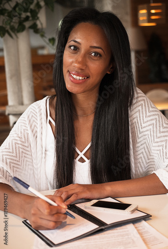 Poster de jardin Bar Portrait of beautiful young black woman sitting at cafe and writ